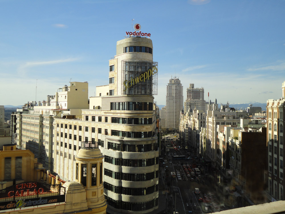 plaza del callao with torre carrin left and gran via leading towards torre de madrid at plaza de espaa mountains in the background