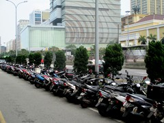 The Macau residents popular scooters stand in contrast to the casino visitors luxury cars.
